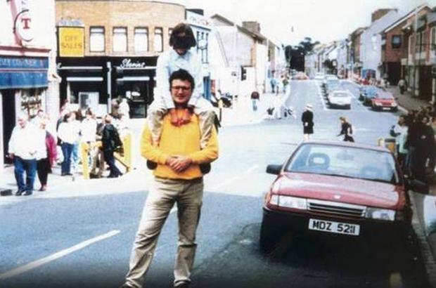 İrlanda'da normal bir gün Biraz sonra başlarına gelecek felaketten habersiz, baba-oğul kırmızı bir arabanın yanında fotoğraf çektiriyorlardı. 1998 yılıydı ve İrlanda'da 30 yıl süren etnik milliyetçilik çatışmasının baş aktörü IRA'nın bu arabaya bomba yüklediğinden o an kimsenin haberi yoktu. Fakat daha sonra kamuoyu 29 kişinin ölümüne, 200 kişinin de yaralanmasına sebep olan bu patlamayla ilgili, en yüksek ölüm oranına sahip terör olayı olmasını yıllarca tartıştı. Fotoğrafın çekildiği makine, bomba enkazından bulunduktan sonra basınla paylaşıldı.