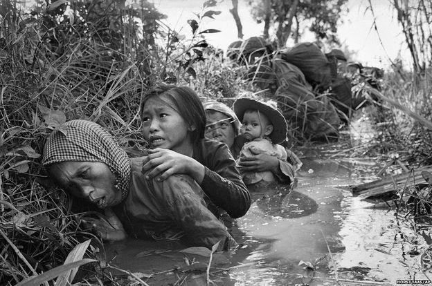 Faas, Saygon'dayken savaşın korkunçluğunu yansıtan birçok fotoğrafı çekecek olan genç Vietnamlı foto muhabirlerini eğitmiş, onlara yol göstermişti. Vietnamlı muhabirlerin her gün çektikleri fotoğraflar dünyanın karşılıklı ateş arasında kalan insanların yaşadığı travmaları tüm dünyanın öğrenmesini sağladı. Bu fotoğrafta kadın ve çocukların Saygon yakınlarında süren şiddetli ateşten korunmaya çalışmaları görüntüleniyor. (1 Ocak 1966)