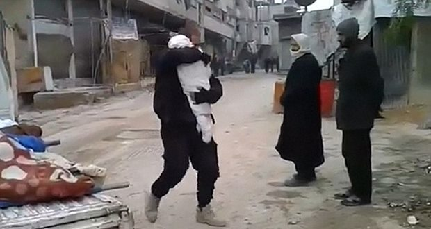 Footage shows man carrying body dead child Syria. Video